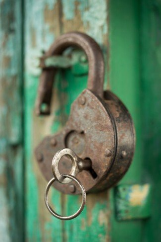 old padlock with key on a green wooden wall