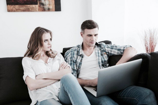 Unhappy woman sitting while her husband working with laptop