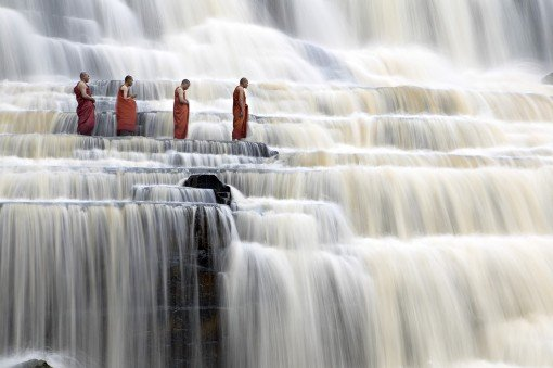 monks in waterfall