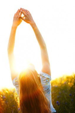 Young woman enjoying sunlight with raised arms